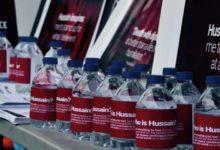 """صورة """"شيعة ويفز"""" ترصد حملات لتوزيع زجاجات الماء البارد وأخرى لـ """"توزيع اللقاح"""" باسم الإمام الحسين (عليه السلام)"""