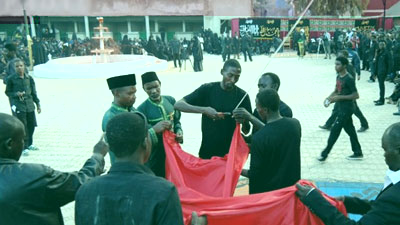 Hoisting the black flag of Imam Hussein above the dome of a Husainiyyah in Nigeria