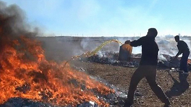 Photo of IS burning books at Iraq libraries and loading artifacts onto refrigerated trucks at night