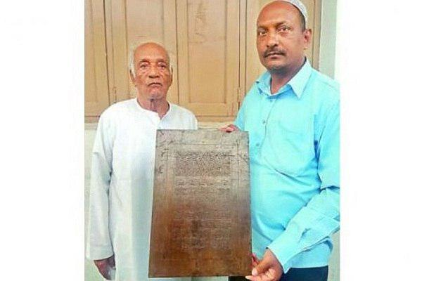 Photo of Family in Hyderabad, India, engraving Quran verses on iron plaques