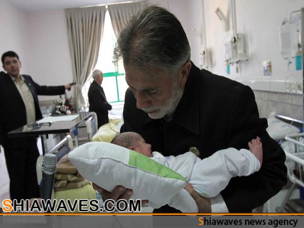 تصویر بانگ مسلمانی در گوش نوزادان مشهدي ، توسط خادمان حرم رضوي
