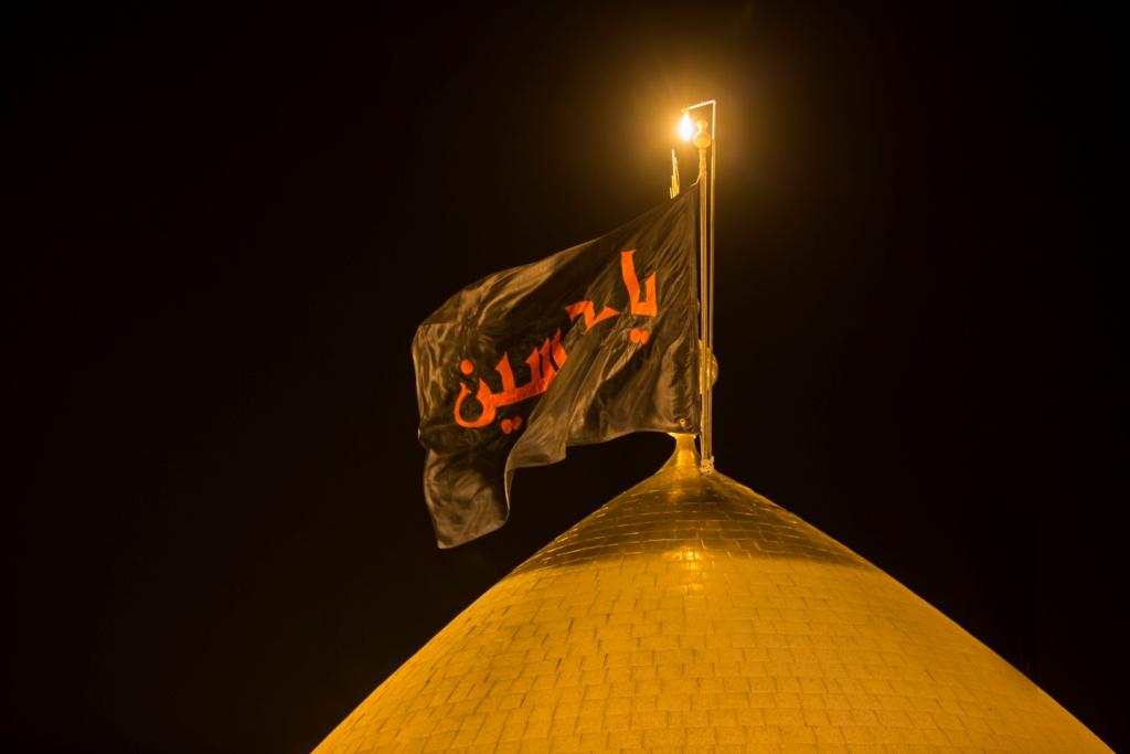 تصویر تعويض پرچم گنبد حرم مطهر حسينى به نشانه آغاز ماه حزن واندوه، محرم الحرام