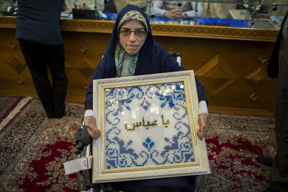 تصویر عرض ارادت یک معلول با ساختن تابلویی به کمک دندانهای خود و اهدای آن به آستان مقدس عباسی