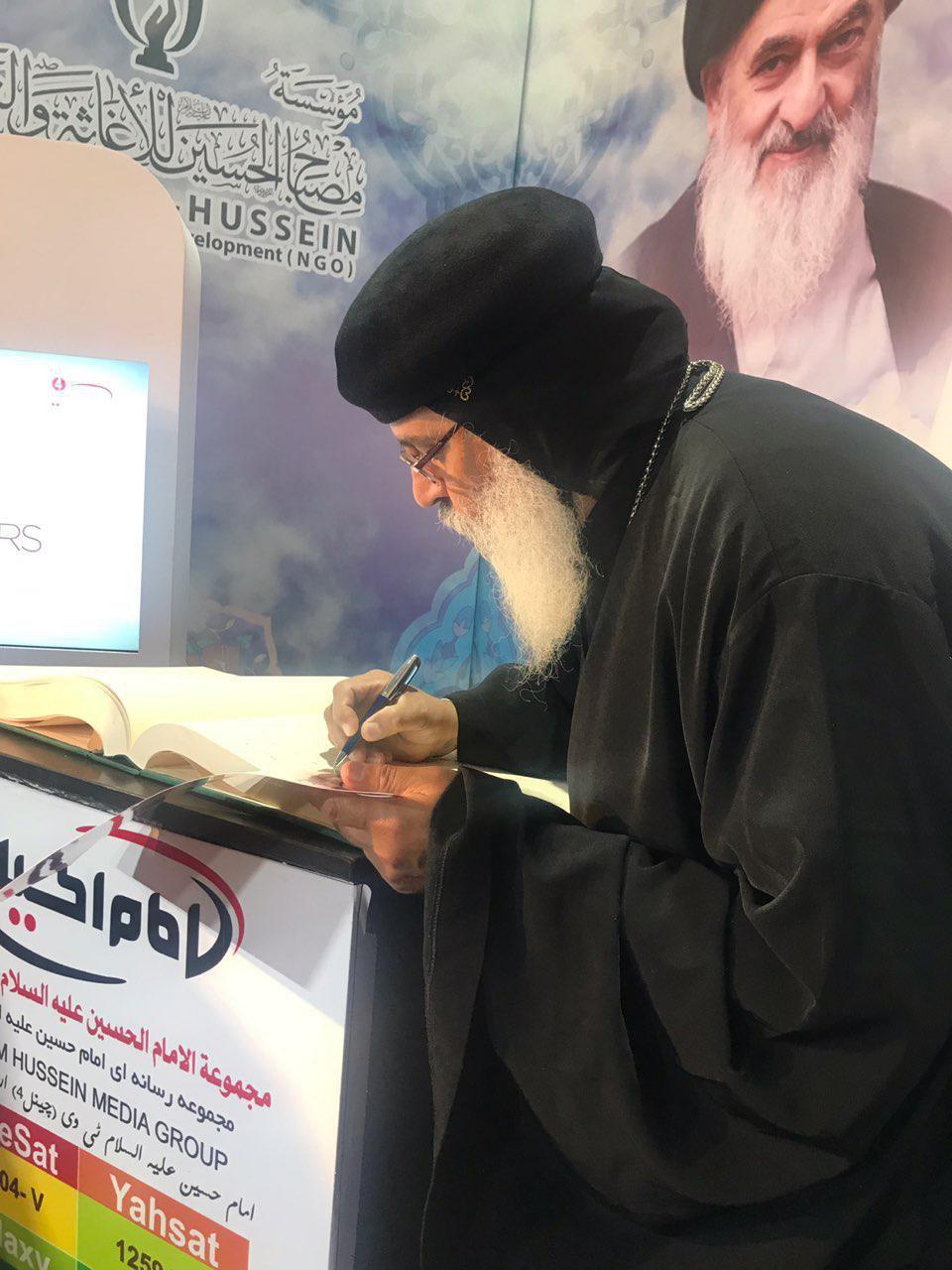 تصویر حضور رهبر قبطی های عراق در غرفه مجموعه رسانه ای امام حسین علیه السلام در نمایشگاه بین المللی بغداد